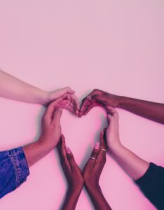 Hands of many ethnicites coming to gether to form a heart shape